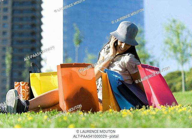 Young woman sitting on ground surrounded by shopping bags, talking on cell phone
