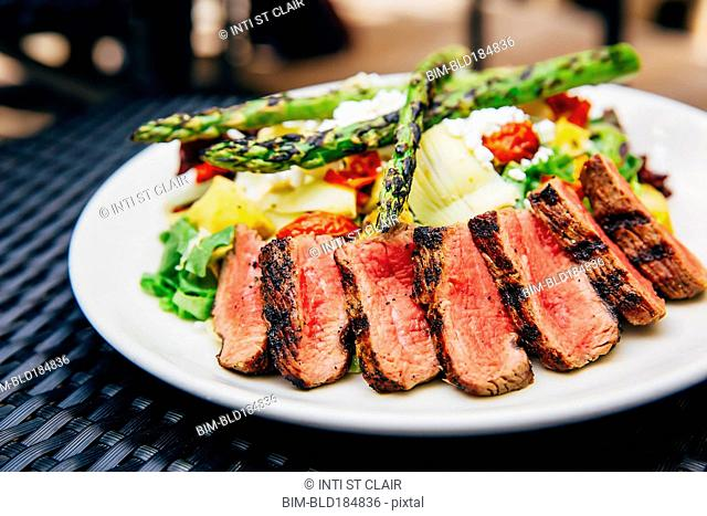 Plate of grilled meat and asparagus salad