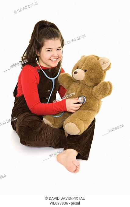 Caucasian child using a stethoscope to pretend she is listening to her teddybear's heart beat