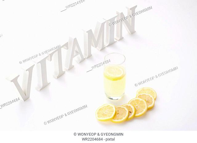 High angle of solid word VITAMIN standing with a glass of lemonade and slices of lemon