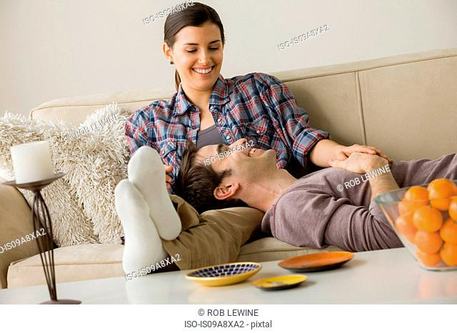 Couple on sofa, man with head on woman's lap