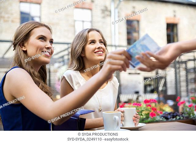 young women paying for coffee at street cafe
