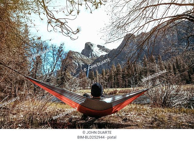 Caucasian man laying in hammock near mountains