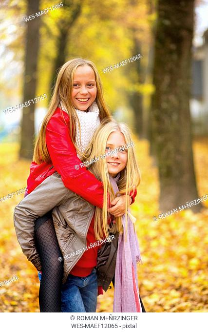 Girl giving her best friend a piggyback ride in autumn