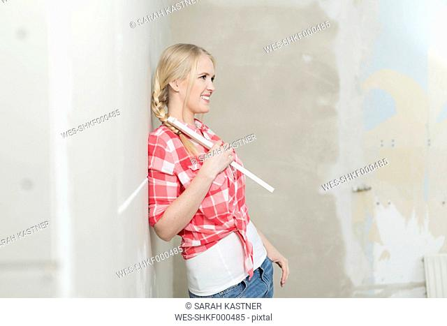 Smiling young woman with pocket rule on construction site