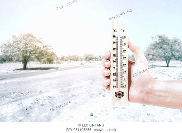 Hand holding thermometer measuring the temperature outdoor with a clear sky background. Heatwave concept