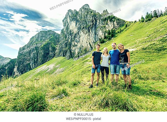 Germany, Bavaria, Pfronten, portrait of happy family on alpine meadow near Aggenstein