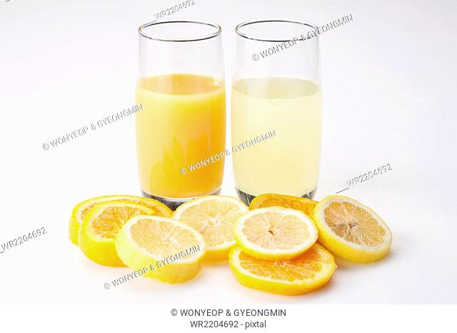 Glass of orange juice and a glass of lemonade with slices of orange and lemon