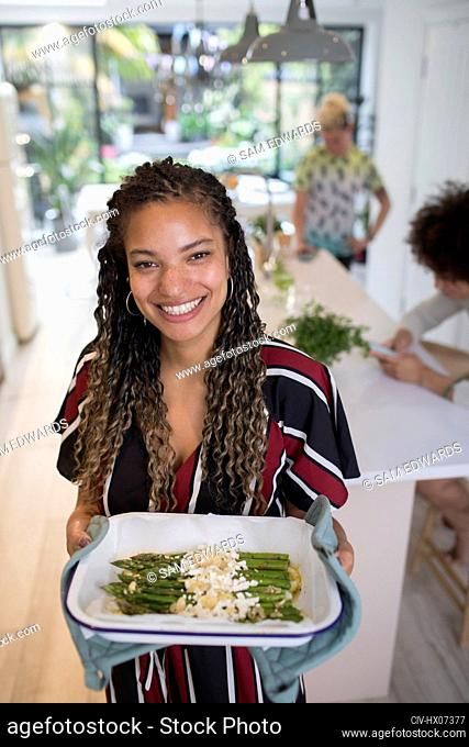 Portrait happy woman cooking asparagus in kitchen