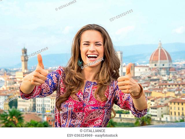 Smiling young woman showing thumbs up against panoramic view of florence, italy