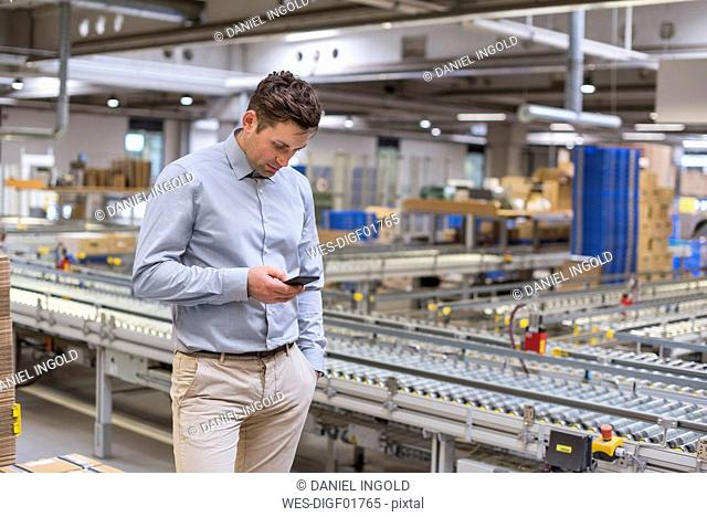 Man at conveyor belt in factory looking at cell phone