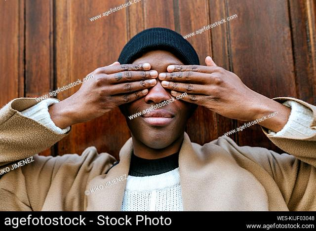 Young woman covering eyes with hands against wooden wall