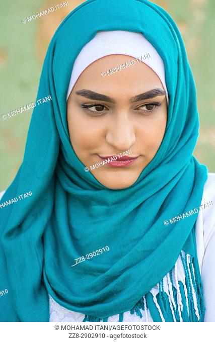 Beautiful young Muslim woman wearing hijab looking away