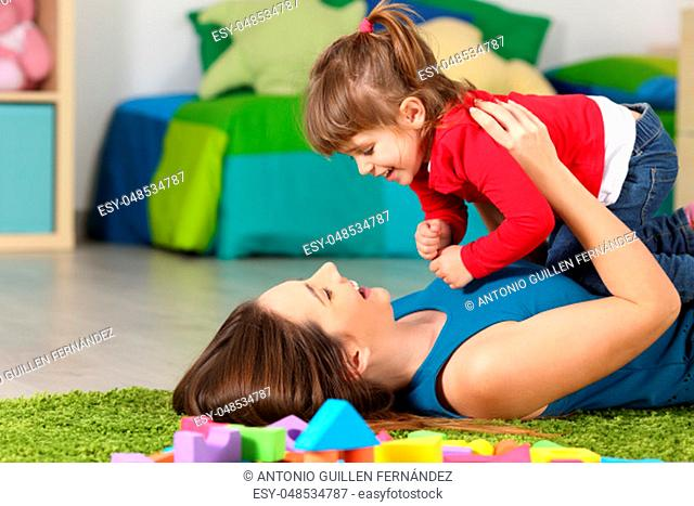 Happy mother playing with her daughter lying on a green carpet in the bedroom at home