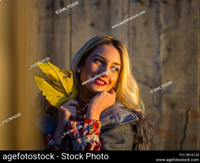 Young woman is holding big Yellow-Green Autumnal leaf in hand looking away smiling