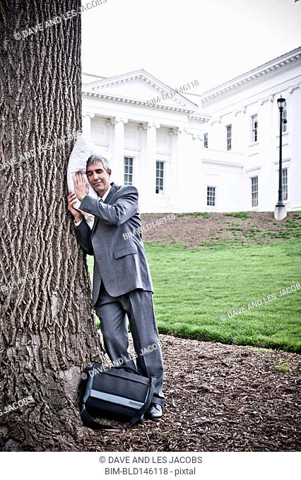 Businessman with pillow sleeping against tree trunk