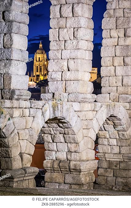 Partial view of the Roman aqueduct located in the city of Segovia at night, between one of the arches the cathedral is observed, Unesco World Heritage Site