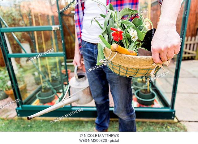 Close-up of man holding basket with flowers and watering can before greenhouse in garden