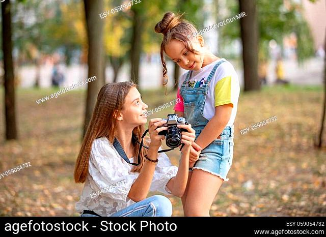 Two girls on the street make a video for the Internet, record a video blog for the camera. Children with photo appart in a city park