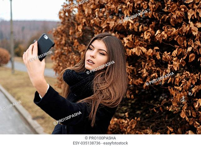 Pretty girl taking selfie at the nice park