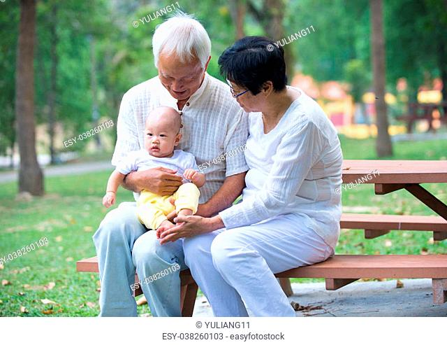 chinese grandfather playing with baby grandson at outdoor