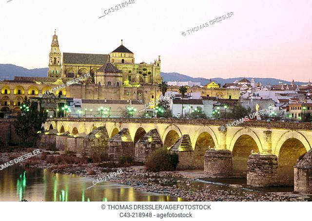 Puente Romano spanning the Guadalquivir River and the Merzquita at dusk. Córdoba. Andalusia. Spain