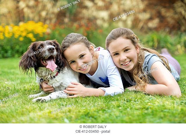 Smiling girls relaxing with dog on lawn