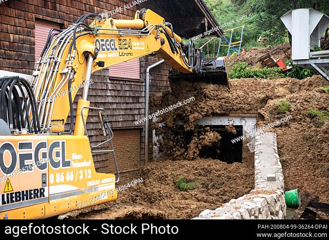 04 August 2020, Bavaria, Vachenlueg: With an excavator shovel, a man lifts sludge from the driveway of a residential house