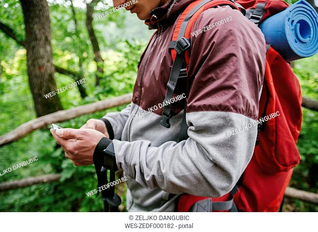Serbia, Rakovac, young man using smartphone during hiking