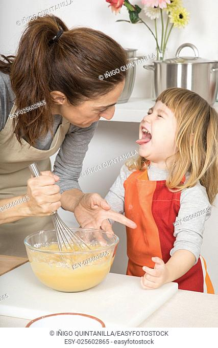 three years old child with dislike or disgust face expression after taste whipped cream, next to woman, in teamwork, making and cooking a sponge cake at kitchen...