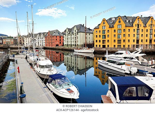 Pleasure boats moored along the Alesundet Canal in Alesund, Norway. In the background are Art Nouveau-style buildings for which the city is famous