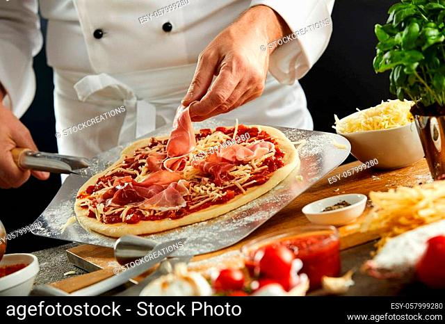 Chef making a parma or prosciutto ham Italian pizza in a close up view of his hands placing the meat on the mozzarella cheese and tomato