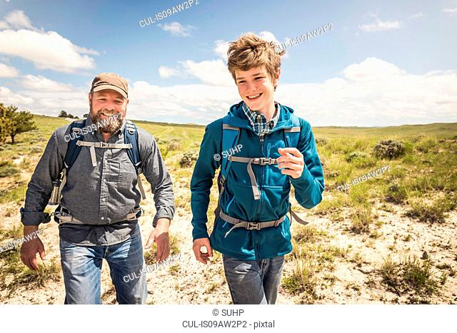 Father and teenage son racing each other on hiking trip, Cody, Wyoming, USA