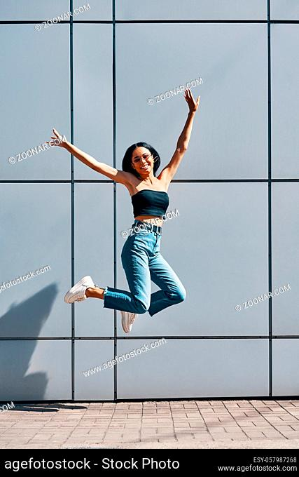 Portrait of cheerful positive black girl jumping in the air on wall street urban background
