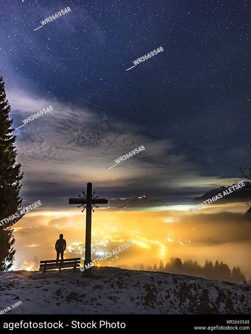 Silhouette of man admiring illuminated valley at night