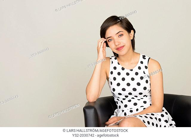 Young woman with dotted dress sitting in leather armchair.1015