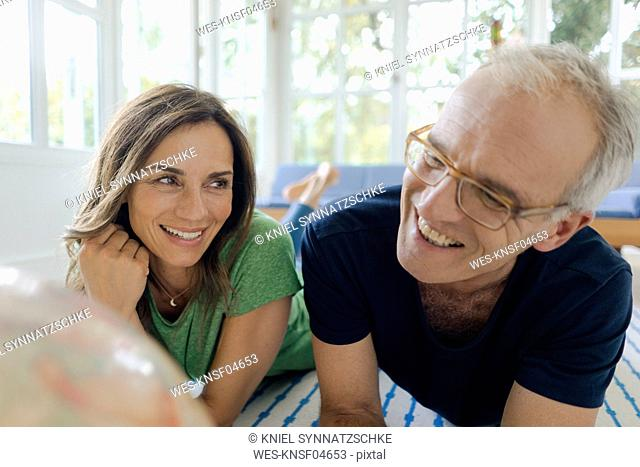 Happy mature couple lying on the floor at home looking at globe