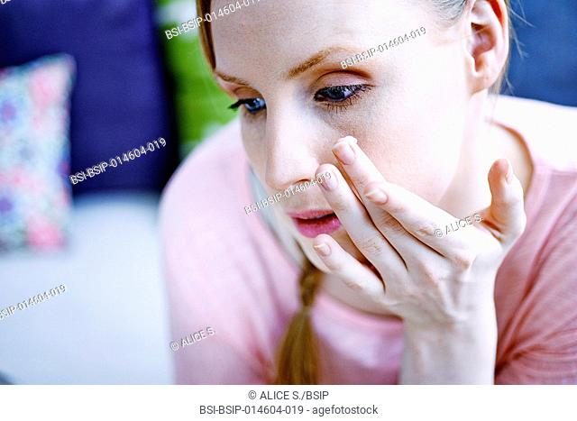 Woman applying cream on her face