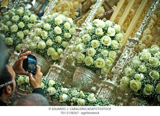 Man taking a photo with his mobile phone in the Holy Week in Seville
