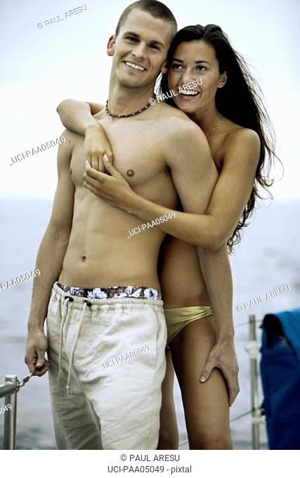 Young couple embracing on sailboat