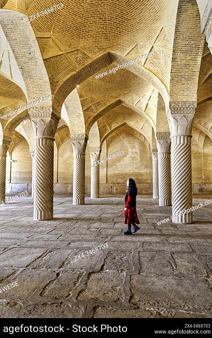 Iranian woman walking through the prayer hall with Shabestan pillars, Vakil Mosque, Shiraz, Fars Province, Iran