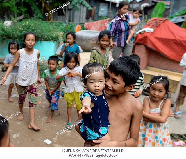 A group of children stands in the Chhba Anmpov Slum on the grounds of a Chinese graveyard in Phnom Penh, Cambodia, 10 December 2013