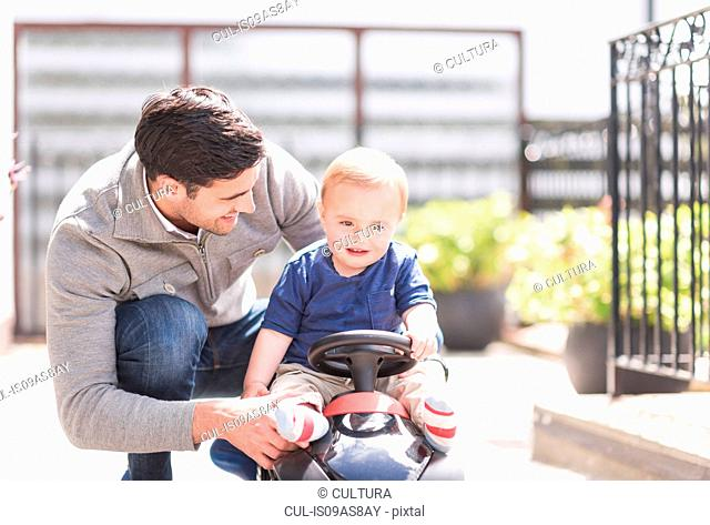 Father and and young son playing together, son riding toy car