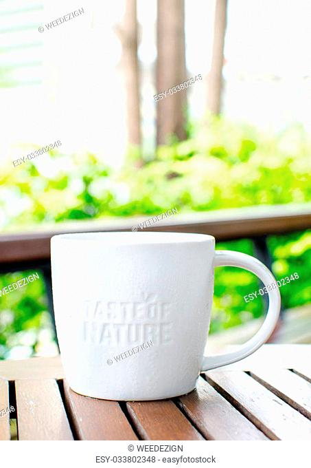 "White ceramic mug with stamp word """"Taste of nature"""" at coffee shop in garden"