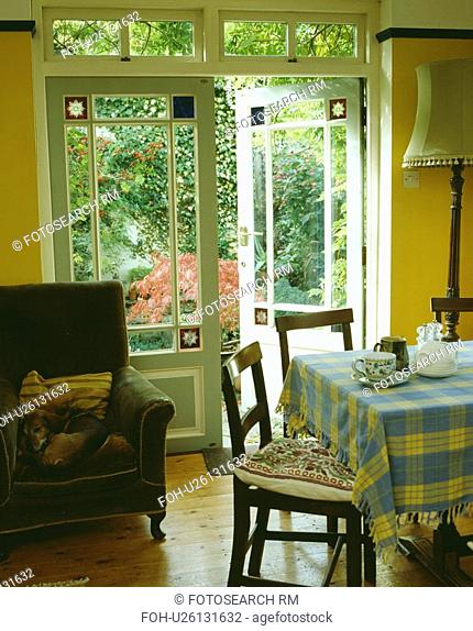 Checked cloth on table in diningroom with green armchair beside open French doors with stained glass detail