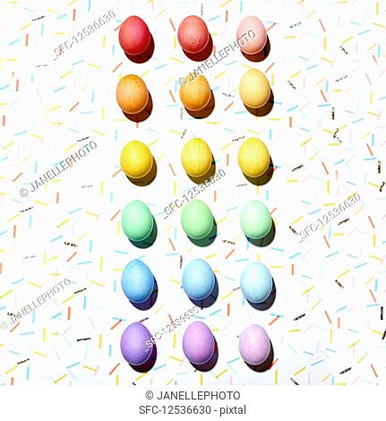 Colourful Easter eggs arranged in a colour gradient (top view)
