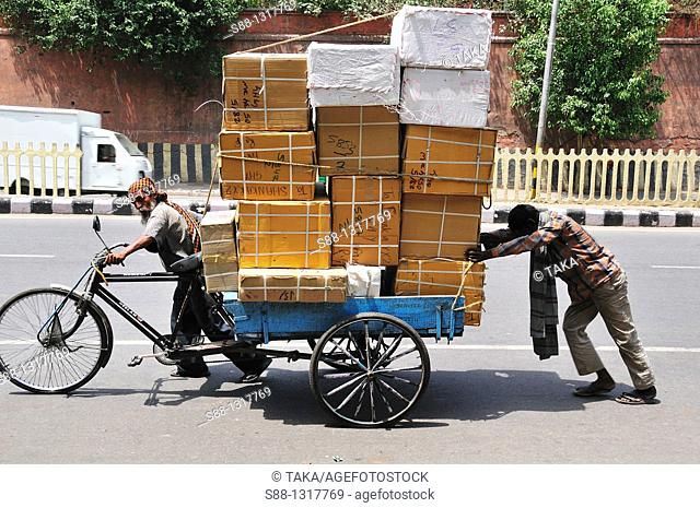 Two men carrying huge boxes, Delhi India