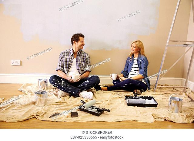 Expectant Couple Taking A Break Whilst Decorating Nursery