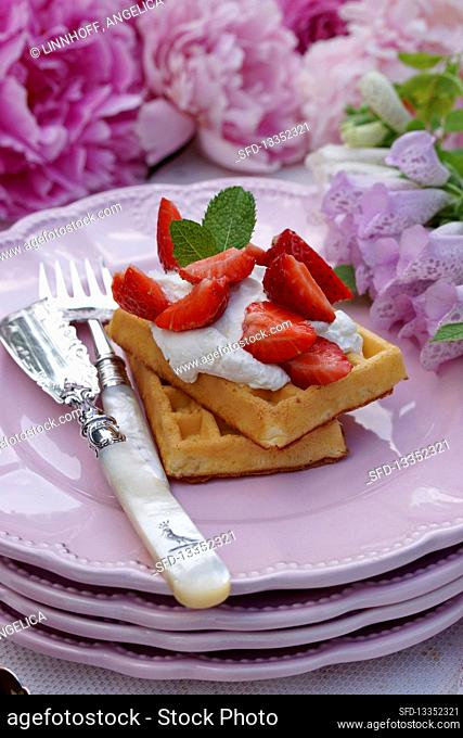 Waffles with strawberries, cream and mint leaves