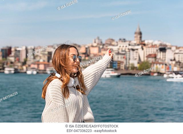 Portrait of beautiful attractive young girl with headphones and smartphone and sunglasses shows Galata Tower in Istanbul, Turkey